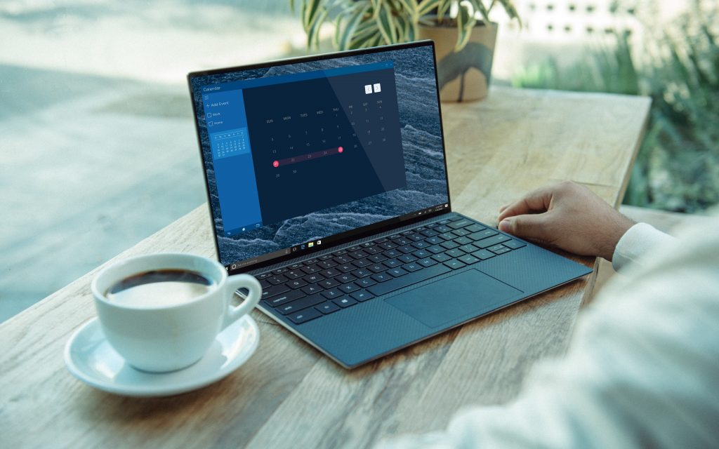 Image of an open laptop displaying a calendar, next to a cup of coffee.